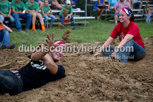 Sarah Shaw/The Herald  Cole Kreilein of Jasper tossed dirt at a fan while waiting for the adult tug-of-war competition to begin at the Dubois County 4-H Fairgrounds in Bretzville on Thursday evening, while Elizabeth Brinkman of Ferdinand looked on.