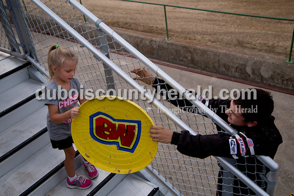 """Sarah Shaw/The Herald  """"Bully Warrior"""" driver Blaine Schoenfeld of Rosebud, Mo., 15, gave the shield from his truck to Arianna Talbert of Haysville, 4, after his truck was damaged during the Mini Monster Truck show at the Dubois County 4-H Fairgrounds in Bretzville on Tuesday. Lil Monster Trucks, a professional mini monster truck team out of St. Louis, visited the Dubois County 4-H Fair for the first time this year. Seven drivers, ages 6 to 15 raced and performed freestyle tricks."""