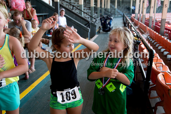 """Sarah Shaw/The Herald  Nora Breitwieser of Jasper, 7, and Heidi Giannini of Newburgh, 8, danced to the """"Cha Cha Slide"""" during the the Dubois County Youth Triathlon and Duathlon on Saturday at League Stadium in Huntingburg."""