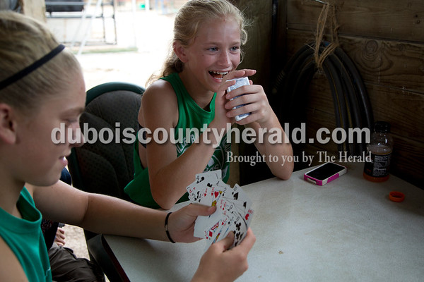 Sarah Shaw/The Herald  Rose Tempel, 13, left, and her sister Marie, 11, both of St. Henry, played cards in the cattle barn at the Dubois County 4-H Fairgrounds in Bretzville on Wednesday.