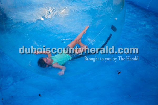 Keira Volz of Huntingburg, 8, floated around a temporary pool in a large blow up ball on Tuesday evening at the Dubois County 4-H Fair in Bretzville. This ride gives kids the chance to feel like they're walking on water, or floating on the surface while staying dry.   Alisha Jucevic/The Herald