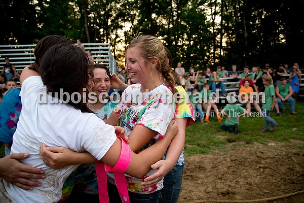 Sarah Shaw/The Herald  Melanie Roberts of Hillham, 17, right, embraced her teammates Katelyn Tretter of Ferdinand, 16, left, and Jennifer Merkley of St. Anthony, 18, after their side won the battle of the queens during the tug-of-war competition at the Dubois County 4-H Fairgrounds in Bretzville on Thursday evening.