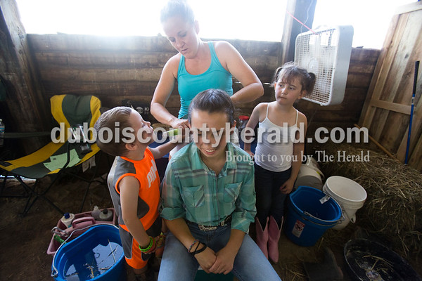 Sarah Ann Jump/The Herald Audra Schue of Jasper braided the hair of her niece Abby Fischer of Jasper, 14, as her children Quinten Schue, 4, left, and Ella Schue, 6, right, looked on before the beef show at the Dubois County 4-H Fairgrounds in Bretzville on Thursday.