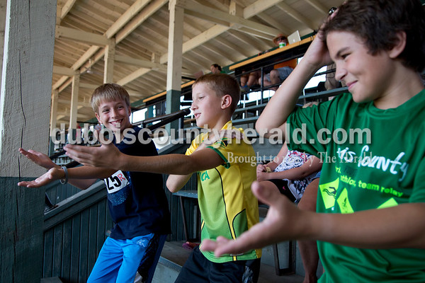 """Sarah Shaw/The Herald  Cameron Tooley of Huntingburg, 11, Cole Writhwein of Huntingburg, 11, and Reilly Lechner of Holland, 11, danced to the """"Macarena"""" after the Dubois County Youth Triathlon and Duathlon on Saturday at League Stadium in Huntingburg."""