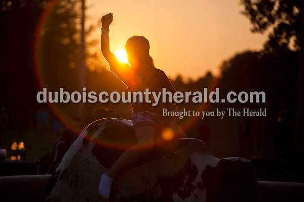 Aurora Jacob of Ferdinand, 7, rode the mechanical bull Wednesday evening at the Dubois County 4-H Fair in Bretzville.  Alisha Jucevic/The Herald