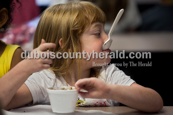 Taylor Commens of Dale, 4, enjoyed a cup of chocolate ice cream during the Hutningburg Public Library ice cream bash on Thursday at Holland Elementary.  Alisha Jucevic/The Herald
