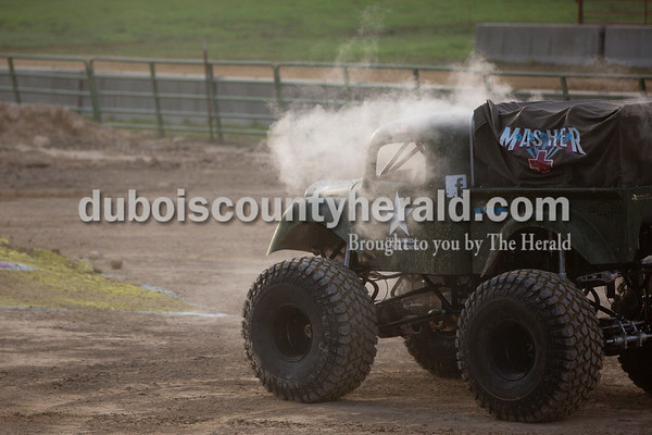 """Sarah Shaw/The Herald  The """"Masher,"""" driven by Kaleb Hustedde of Eureka, Mo., 14, billowed with steam after taking a hard hit during the Mini Monster Truck show at the Dubois County 4-H Fairgrounds in Bretzville on Tuesday. Lil Monster Trucks, a professional mini monster truck team out of St. Louis, visited the Dubois County 4-H Fair for the first time this year. Seven drivers, ages 6 to 15 raced and performed freestyle tricks."""