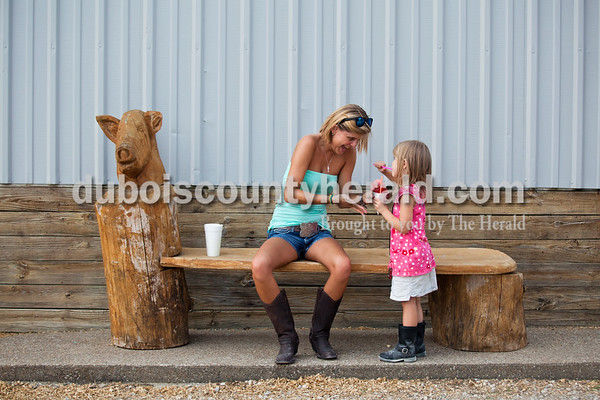 Janelle Mehling of St. Anthony shared a strawberry snow cone with her niece Aylnn Gogel of St. Henry, 3, outside the swine barn Tuesday evening at the Dubois County 4-H Fairgrounds in Bretzville. The fair kicked off this evening and will continue throughout the week.   Alisha Jucevic/The Herald