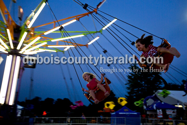 Alivia Hohiemer-Kluesner, 5, and her cousin Isabella Kluesner, 6, both of Jasper twirled around on the swing ride Wednesday night at the Dubois County 4-H Fair in Bretzville.  Alisha Jucevic/The Herald