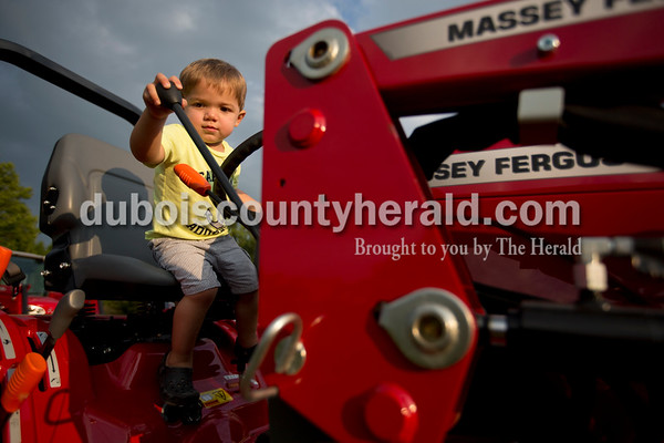 Leo Schaeffer of Ferdinand, 1, tried out one of the tractors at the Hopf Equipment farm machinery display Wednesday night at the Dubois County 4-H Fair in Bretzville.  Alisha Jucevic/The Herald