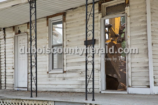 Sarah Ann Jump/The Herald A backhoe was seen through the doorway during the demolition of the house on the corner of 12th and Main streets in Jasper on Tuesday.