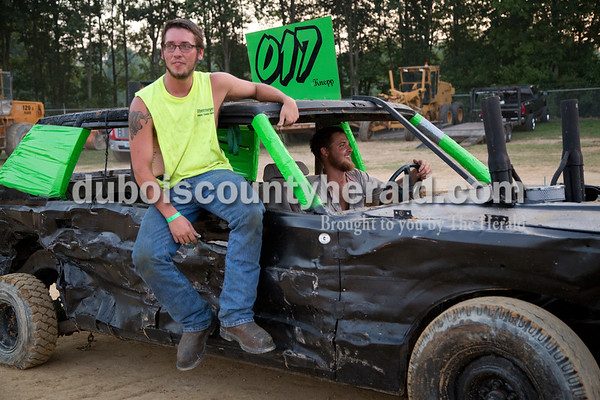 Sarah Shaw/The Herald  Marcus Butcher hitched a ride with Myron Knepp, both of Montgomery, as Knepp's car was towed off the track following the demolition derby at the Dubois County 4-H Fairgrounds in Bretzville on Saturday.