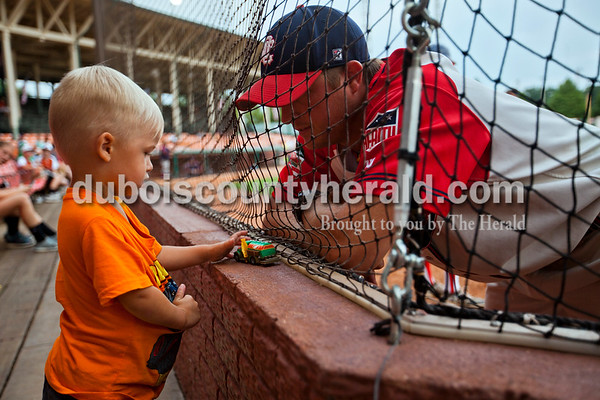 Pitching coach Greg Gogel said hi to his son, Knox, 2, both of Huntingburg, during a break in Monday night's game at League Stadium in Huntingburg. The Bombers defeated the Paducah Chiefs 7-5. Alisha Jucevic/The Herald