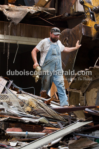Sarah Ann Jump/The Herald Lechner Excavating Inc. employee Bucky Seitz of Jasper retrieved an elephant statue during the demolition of the house on the corner of 12th and Main streets in Jasper on Tuesday.