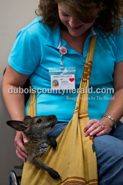 Children's librarian Lisa McWilliams of Huntingburg held a baby wallaby in a shoulder bag during Animal Tales' Nature's Olympians presentation Tuesday afternoon at the Jasper Public Library. Alisha Jucevic/The Herald