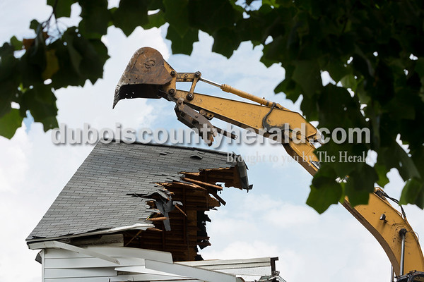 Sarah Ann Jump/The Herald A backhoe operated by Darron Fancher of Petersburg readied to bring down the remainder of the roof during the demolition of the house on the corner of 12th and Main streets in Jasper on Tuesday.