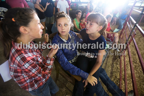 Sarah Ann Jump/The Herald Riley Verkamp of Ireland, 12, left, Allyson Werner of Ferdinand, 14, and Cheyenne Scherle of Ireland, 11, talked about their cows' names as they waited for the beef show to begin at the Dubois County 4-H Fairgrounds in Bretzville on Thursday.