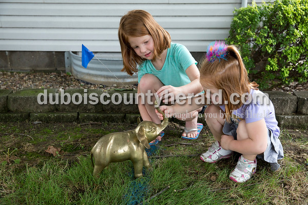 Sarah Ann Jump/The Herald Norah Desser of Jasper, 6, and her sister Penny, 3, looked at an elephant statue that was salvaged from the house, after it was washed, during the demolition of the house on the corner of 12th and Main streets in Jasper on Tuesday.