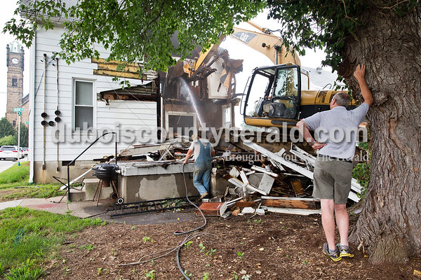 """Sarah Ann Jump/The Herald Property owner Greg Kendall of Jasper, right, watched as Lechner Excavating Inc. employees Bucky Seitz of Jasper and Darron Fancher of Petersburg demolished his rental house on the corner of 12th and Main streets in Jasper on Tuesday. Kendall said the house had reached a point where it was irreparable. """"One of the biggest reasons I'm tearing the house down is that I'm slowing down as far as work goes and I'm trying to eliminate anything that is a pain in my neck. I'm trying to simplify my life,"""" said Kendall, who also owns Greg's Barber Shop next door. """"The barber shop will look nice with a yard,"""" he added."""