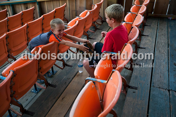Carson Mitchell, 6, left, and his brother Braxton, 10, both of Schnellville, played with a ball and mitt as they watched the Bombers' first matchup in the Ohio Valley League playoffs on Monday night at League Stadium in Huntingburg. The Bombers defeated the Paducah Chiefs 7-5. Alisha Jucevic/The Herald