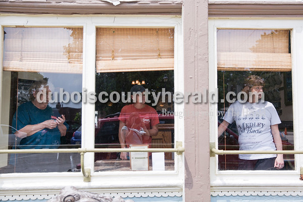 Sarah Ann Jump/The Herald Joan Clark of Jasper, left, Kim Mitchell of Ireland and Peggy Snyder of Birdseye watched through the window of Snap's Restaurant during the demolition of the house on the corner of 12th and Main streets in Jasper on Tuesday.
