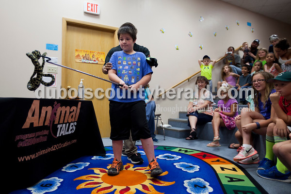 """Evan Radcliff of Oden, 6, held onto a coastal carpet python during Animal Tales' Nature's Olympians presentation Tuesday afternoon at the Jasper Public Library. The program featured seven exotic animals from around the world that utilize unique abilities to adapt  and survive out in the wild. The python is named """"Cuddles"""" because of it's squeezing and wrapping movement. Naturalist Riko Herrera stood behind Radcliff and explained how the camouflage skin helps the snake stay safe and hunt in the wild.  Alisha Jucevic/The Herald"""