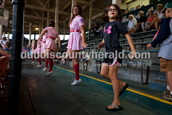 """Riley Blessinger of Huntingburg, 7, danced to """"Cotton Eye Joe"""" with Rockford Peach Jaclyn Altstadt of Huntingburg, left, during the Bombers' first matchup in the Ohio Valley League playoffs on Monday night at League Stadium in Huntingburg. The Bombers defeated the Paducah Chiefs 7-5. Alisha Jucevic/The Herald"""