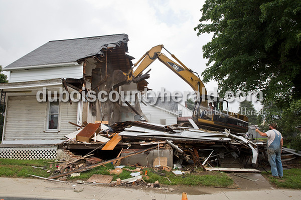 Sarah Ann Jump/The Herald Lechner Excavating Inc. employees Darron Fancher of Petersburg, operating the backhoe, and Bucky Seitz of Jasper demolished the house on the corner of 12th and Main streets in Jasper on Tuesday.