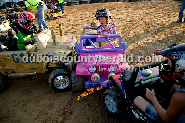 Sarah Shaw/The Herald  Abigail Conrad of French Lick, 6, reacted after being hit by Ryland Gerber of Winslow, 4, left, and Adam Onyette of Petersburg, 6, during the Power Wheels class of the demolition derby at the Dubois County 4-H Fairgrounds in Bretzville on Saturday.