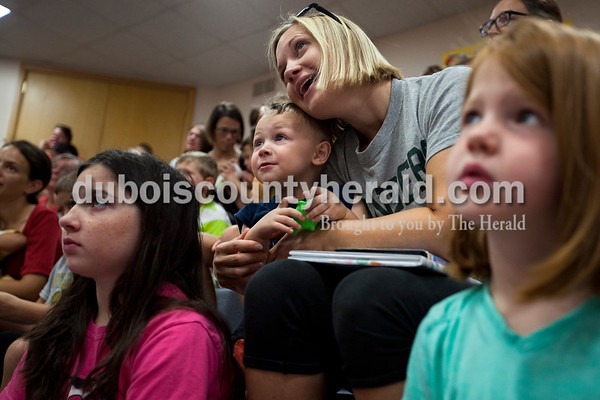 Beth DeSchamp and her son Alex, 2, both of Jasper, watched the Animal Tales' Nature's Olympians presentation Tuesday afternoon at the Jasper Public Library. Carlee Rogers of Jasper, 9, left, and Norah Desser of Jasper, 6, right, sat on either side of them to watch the show.   Alisha Jucevic/The Herald
