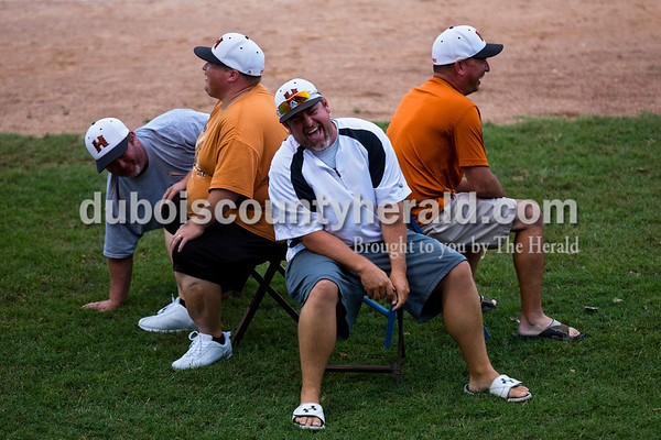 Tell City Hurricanes youth baseball coaches Corey Jennings, center, Brady Meserve, left, Phil Fortwendel, right, and Phillip Ball, back, all of Tell City, played musical chairs during the Bombers' first matchup in the Ohio Valley League playoffs on Monday night at League Stadium in Huntingburg. The Bombers defeated the Paducah Chiefs 7-5. Alisha Jucevic/The Herald
