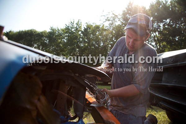 Sarah Shaw/The Herald  Dylan Durcholz of Ferdinand wired the front end of his car before the demolition derby at the Dubois County 4-H Fairgrounds in Bretzville on Saturday.