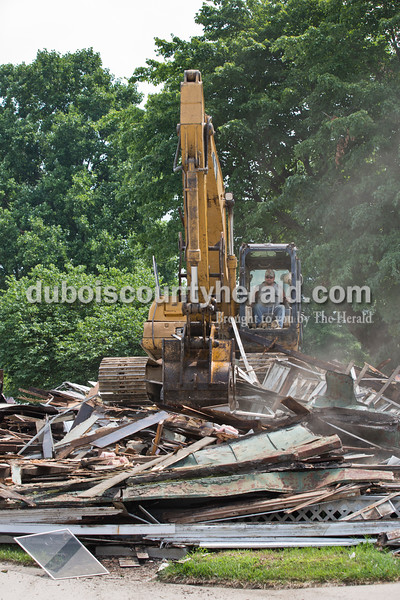 Sarah Ann Jump/The Herald Backhoe operator Darron Fancher of Petersburg sat on the pile of rubble during the demolition of the house on the corner of 12th and Main streets in Jasper on Tuesday.
