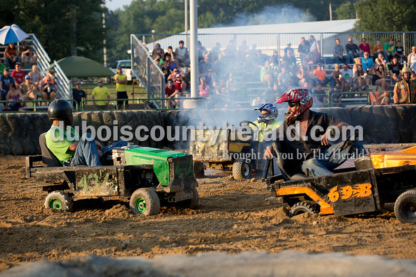 Sarah Shaw/The Herald  From left, Joey Allen, Dave Lampert and Brandon Epple watched the rest of the lawnmower derby after being eliminated during the demolition derby at the Dubois County 4-H Fairgrounds in Bretzville on Saturday.