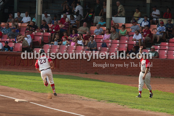 Sarah Ann Jump/The Herald Dubois County Bombers third-base coach Nick Gobert waved Conor Moroder in toward home plate during Wednesday evening's Dubois County Bombers game against the Muhlenberg County Stallions at League Stadium in Huntingburg. The Bombers won 5-1.