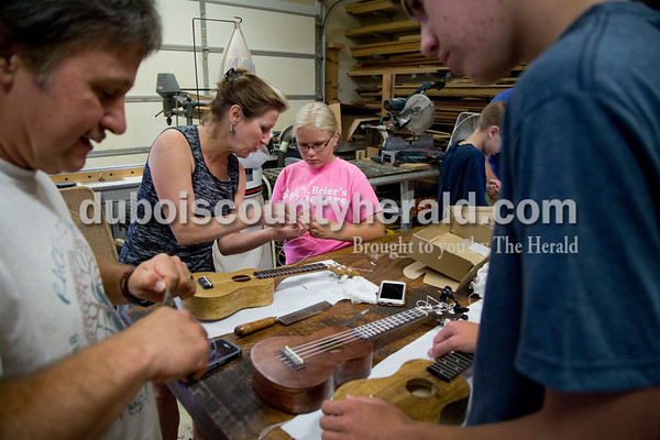 Sarah Shaw/The Herald Kris Lasher of Ferdinand, center left, showed Lauren Klem of St. Anthony, 10, how to string her ukulele while Project A.C.O.R.N. co-chair Rock Emmert of Ferdinand helped Jacob Berg of Ferdinand, 14, during the Project A.C.O.R.N ukulele-making workshop in Ferdinand on Saturday. Inspired by the Ferdinand Folk Festival, Project A.C.O.R.N., standing for Art, Community, Originality, Rhythm, and Nature, is a new community outreach group in Ferdinand that strives to provide learning opportunities for youth and amateurs of all ages in the areas of music, art, environment, and wellness. The group hosted a three-week ukulele-making workshop for both children and adults. Over 30 ukuleles were built during the workshops. The group hopes to offer a ukulele class in the fall so that participants can learn to play their new instruments.