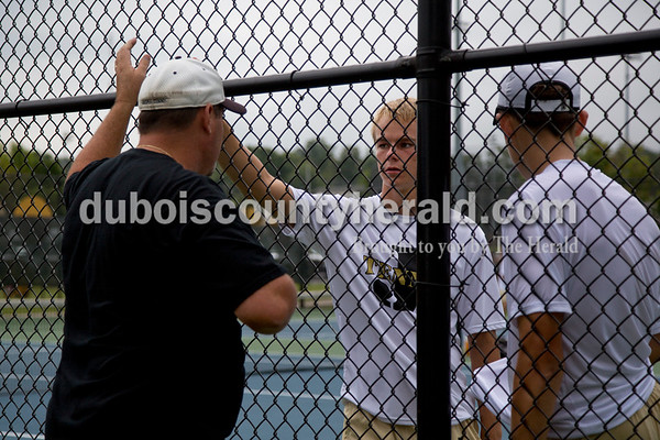 Sarah Shaw/The Herald Jasper head coach Scott Yarbrough talked with Andrew Schmitt and Noah Mendel in between sets of their doubles match against Castle at the tennis invitational in Jasper on Saturday.
