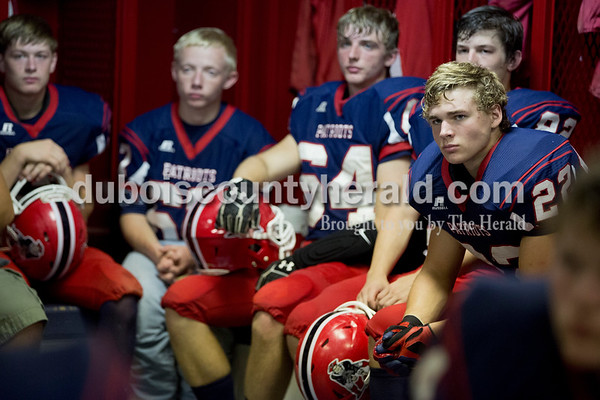 Heritage Hills' Malachi Yeager, right, listened as Patriots head coach Todd Wilkerson spoke to the team in the locker room before the start of the game against Tell City in Lincoln City on Friday. The Patriots beat the Marksmen 20-3.  Sarah Shaw/The Herald