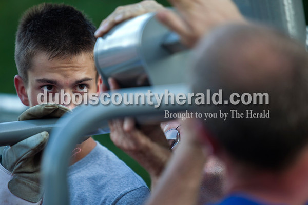 Nick Hedinger of Jasper, 17, started putting the final pieces on the equipment at a new adult handicap accessible fitness center just below Azura Cafe near the Riverwalk on Wednesday evening.  Alisha Jucevic/The Herald