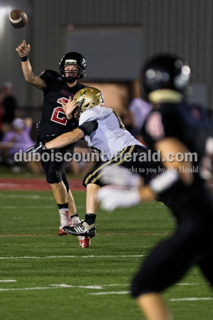 Southridge quarterback Jayce Harter released a pass to Nolan O'Brien as Jasper's Brandon Jochim dove for a tackle during Friday night's game in Huntingburg. The Raiders defeated the Wildcats 28-21, securing the first rivalry win since 2008.  Alisha Jucevic/The Herald