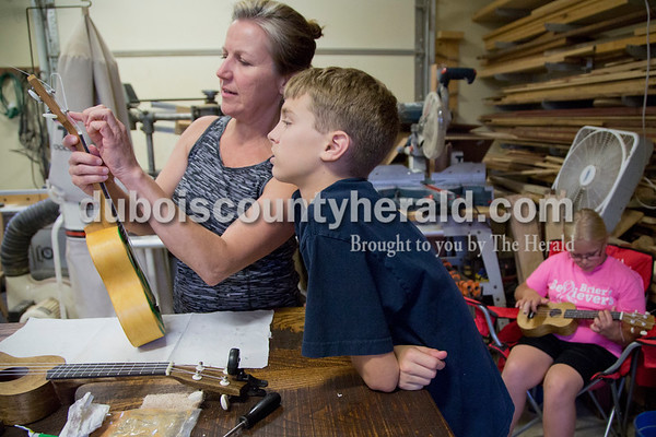 Sarah Shaw/The Herald Kris Lasher of Ferdinand helped Brice Austin of Birdseye, 13, string his ukulele while Lauren Klem of St. Anthony, 10, strummed hers during the Project A.C.O.R.N ukulele-making workshop in Ferdinand on Saturday. Inspired by the Ferdinand Folk Festival, Project A.C.O.R.N., standing for Art, Community, Originality, Rhythm, and Nature, is a new community outreach group in Ferdinand that strives to provide learning opportunities for youth and amateurs of all ages in the areas of music, art, environment, and wellness. The group hosted a three-week ukulele-making workshop for both children and adults. Over 30 ukuleles were built during the workshops. The group hopes to offer a ukulele class in the fall so that participants can learn to play their new instruments.