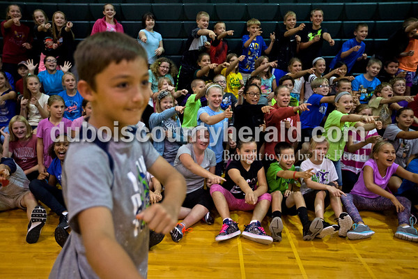"""Cedar Crest Intermediate School fifth-grader Sage Stout, left, and sixth grader Lydia Betz, not pictured, led their classmates in the roller coaster cheer before the student spread out on the gym floor to watch """"Inside Out"""" on Monday afternoon in Bretzville. As a prize for completing all 25 bingo squares in their summer reading program, 100 students qualified for pizza and a movie after school. Librarian Dorothy Buechler said the program gave the students new and interesting ways to incorporate reading into their summer. The squares included things like reading a comic book or poem, listening to an audio book, reading a newspaper article and reading chapter books.  Alisha Jucevic/The Herald"""