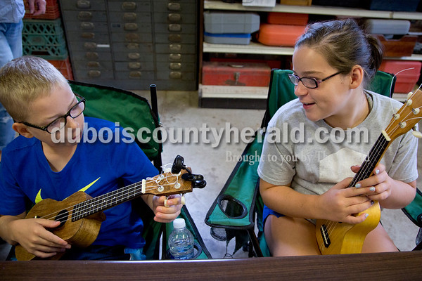 Sarah Shaw/The Herald Mason Tobin of Ferdinand, 10, tuned his ukulele while his cousin Olivia Englert of St. Anthony, 13, watched during the Project A.C.O.R.N ukulele-making workshop in Ferdinand on Saturday. Inspired by the Ferdinand Folk Festival, Project A.C.O.R.N., standing for Art, Community, Originality, Rhythm, and Nature, is a new community outreach group in Ferdinand that strives to provide learning opportunities for youth and amateurs of all ages in the areas of music, art, environment, and wellness. The group hosted a three-week ukulele-making workshop for both children and adults. Over 30 ukuleles were built during the workshops. The group hopes to offer a ukulele class in the fall so that participants can learn to play their new instruments.