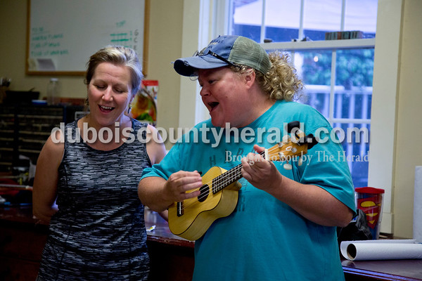 """Sarah Shaw/The Herald Kris Lasher of Ferdinand and Debbie Schuetter of Jasper took a break during the Project A.C.O.R.N ukulele-making workshop to sing John Denver's """"Leaving on a Jet Plane"""" in Ferdinand on Saturday. Both Lasher and Schuetter made ukueles during the evening adult class and came to the children's class on Saturday to help out. Inspired by the Ferdinand Folk Festival, Project A.C.O.R.N., standing for Art, Community, Originality, Rhythm, and Nature, is a new community outreach group in Ferdinand that strives to provide learning opportunities for youth and amateurs of all ages in the areas of music, art, environment, and wellness. The group hosted a three-week ukulele-making workshop for both children and adults. Over 30 ukuleles were built during the workshops. The group hopes to offer a ukulele class in the fall so that participants can learn to play their new instruments."""