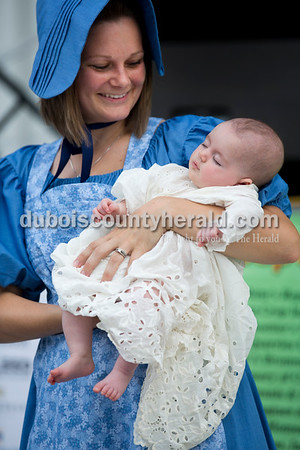 Marci Showalter of Jasper held her 3-month-old daughter Teagan, who slept through the Old Irish Fashion Show, during the Ireland Bicentennial celebration Friday evening. Sarah Ann Jump/The Herald