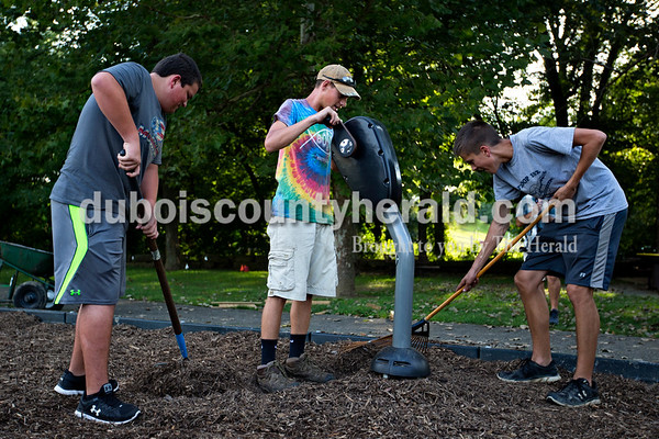 Boy Scout Troop 182 members Eric Brenner, 14, left, and Nick Hedinger, 17, right, worked on spreading mulch as Dallas Lueken, 15, tried out one of the partially set up fitness machines at the new adult handicap accessible fitness center just below Azura Cafe near the Riverwalk on Wednesday evening.   Alisha Jucevic/The Herald