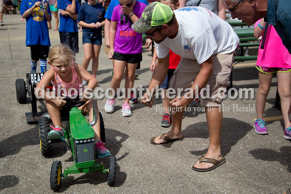 Sarah Shaw/The Herald Todd Andry of Birdseye, right, cheered on his daughter, Addison, 6, while she pedaled in the kiddie tractor pull during the St. Anthony Firemen's Fest in St. Anthony on Saturday.