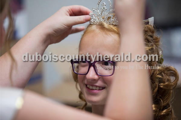2015 Miss Shamrock Queen Nicole Kress of Ireland, 17, let on Jillian Dittelberger of Ireland, 9, try on her crown before the Little Miss and Mister Ireland Bicentennial pageant on Sunday at Ireland Elementary School.  Alisha Jucevic/The Herald