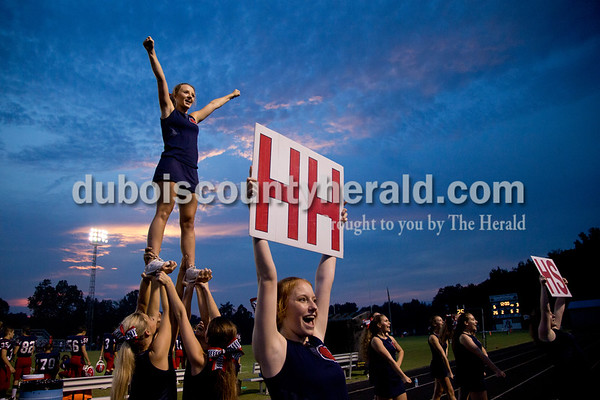 Heritage Hills High School senior Kayla Wilkerson was hoisted into the air while sophomore Emily Frakes, center, helped lead a cheer during the game against Tell City in Lincoln City on Friday. The Patriots beat the Marksmen 20-3.  Sarah Shaw/The Herald