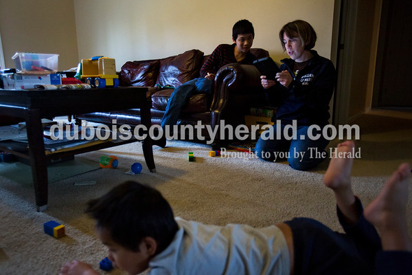 """Samuel's mother, Ashlin, used a translator app to help Samuel find one of his favorite chinese television shows on a tablet at their home in Jasper on April 21 as his brother Mathieu, 4, played with legos next to them. Ashlin adopted Mathieu in January 2014 and adopted Samuel the following summer in July 2015. """"His ability to adapt has been impressive to me,"""" Ashlin said. Samuel knew very little English when he first came home with her, but she said he progressed quickly throughout the year. Ashlin can recognize some Chinese words from a year abroad in Beijing, but often uses a translator app when needed and to help find television shows and audio stories on their tablet."""